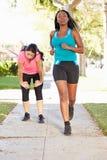 2 женских бегуна работая на пригородной улице Стоковое фото RF