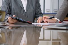 2 женских бухгалтера проверяя финансовый отчет или подсчитывая доходом калькулятора для налоговой формы, конца-вверх рук Стоковая Фотография