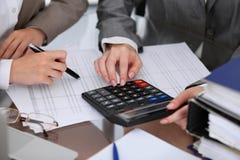 2 женских бухгалтера рассчитывать доход калькулятора для завершения налоговой формы вручают крупный план Налоговое ведомство Стоковое Изображение RF