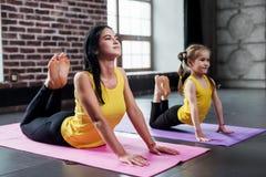 2 женских гимнаста различного времени делая протягивающ тренировку сгабривая назад пробовать касаться голове с тренировкой ног Стоковые Фотографии RF