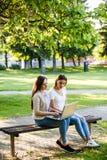 2 женских друз в парке сидя на стенде и работая на lapto Стоковое Изображение