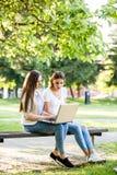 2 женских друз в парке сидя на стенде и работая на lapto Стоковая Фотография