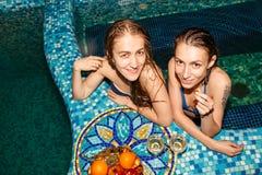 2 женских друз в плавательном бассеине Стоковые Изображения