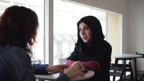 2 женских друз говоря в кафе: молодая мусульманская женщина в черном hijab говорит к ее женскому кавказскому другу пока сток-видео