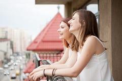2 женских друз говоря и смеясь над на балконе Стоковые Фотографии RF