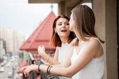 2 женских друз говоря и смеясь над на балконе Стоковое Фото