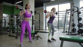 2 женских друз делают назад сидят на корточках в современном спортзале акции видеоматериалы