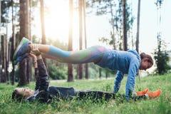 2 женских друз делая планку партнера работают практикуя лес pilates весной Стоковые Фото