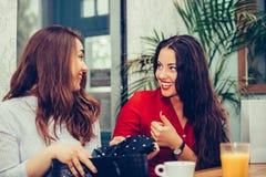 2 женских друз деля их новые приобретения друг с другом стоковые изображения