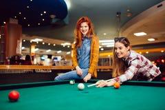 2 женских друз играя снукер Стоковая Фотография