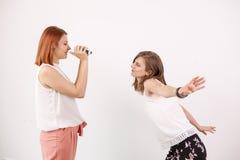 2 женских друз играя с камерой действия Стоковые Фотографии RF