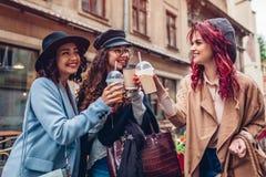 3 женских друз имея пить outdoors Женщины clinking кофе, апельсиновый сок и чашки чая Стоковое Фото