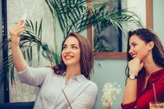 2 женских друз имея потеху в кафе и принимая selfie со смартфоном стоковое изображение