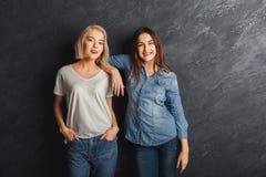 2 женских друз имея потеху на предпосылке студии Стоковые Фотографии RF