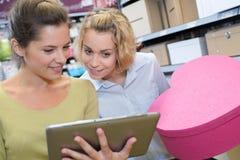 2 женских друз используя таблетку в магазине Стоковые Изображения