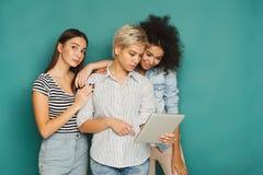 3 женских друз используя таблетку в студии Стоковое фото RF