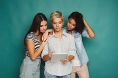 3 женских друз используя таблетку в студии Стоковая Фотография RF
