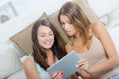 2 женских друз используя таблетку дома Стоковые Фотографии RF