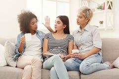 3 женских друз используя таблетку и выпивающ кофе Стоковое фото RF