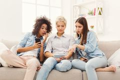 3 женских друз используя smartphones дома Стоковые Фотографии RF