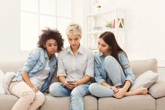 3 женских друз используя smartphones дома Стоковое фото RF