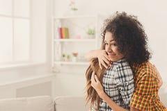 2 женских друз обнимая один другого дома Стоковое Изображение RF