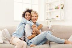 2 женских друз обнимая один другого дома Стоковая Фотография