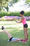 2 женских друз протягивая на парке после jogging Стоковое Изображение RF