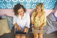2 женских друз работая совместно outdoors на холодном кафе с портативным компьютером, одним кавказцем девушки, другое афро женщин Стоковые Фотографии RF