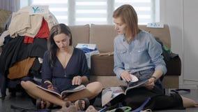 2 женских друз сидят совместно на поле живя комнаты и осматривая журналов, слегка ударяющ страницы и беседовать видеоматериал