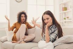 2 женских друз сидя на софе и спорить Стоковая Фотография
