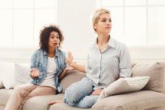 2 женских друз сидя на софе и спорить Стоковое Фото