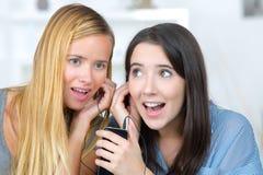2 женских друз слушая такой же переговор стоковое фото rf