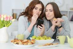 2 женских друз смотря smartphone Стоковые Фото