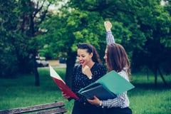 2 женских друз, студенты празднуя успех в парке стоковые изображения rf