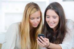 2 женских друз читая текстовое сообщение Стоковая Фотография