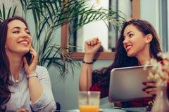 2 женских друз elebrating хорошие новости чтения успеха на планшете стоковые фото
