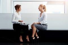 2 женских делового партнера имея приятный переговор после работы на сенсорной панели пока сидящ в интерьере офиса, Стоковое Изображение RF
