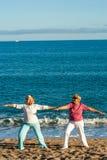 2 женских золотых agers делая йогу на пляже. Стоковое Изображение