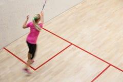 2 женских игрока сквош в быстром действии на суде сквош Стоковая Фотография