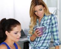 2 женских дизайнера в офисе смотря компьтер-книжку Стоковое Фото