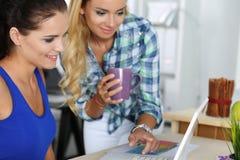 2 женских дизайнера в офисе смотря компьтер-книжку Стоковая Фотография