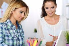 2 женских дизайнера в офисе смотря портативный компьютер Стоковые Фотографии RF