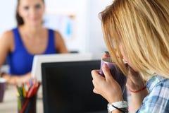 2 женских дизайнера в чае утра офиса выпивая Стоковые Фотографии RF