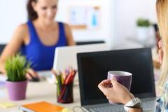 2 женских дизайнера в чае утра офиса выпивая Стоковое Изображение RF