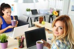 2 женских дизайнера в чае утра офиса выпивая Стоковая Фотография RF