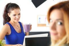 2 женских дизайнера в чае утра офиса выпивая Стоковое Фото