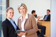 2 женских исполнительной власти используя планшет с встречей офиса в предпосылке Стоковое Фото