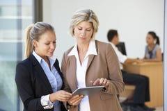 2 женских исполнительной власти смотря планшет с встречей офиса в предпосылке Стоковая Фотография