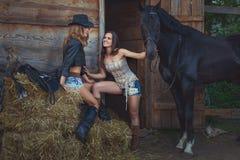 2 женских ковбоя на ферме с лошадями Стоковая Фотография RF